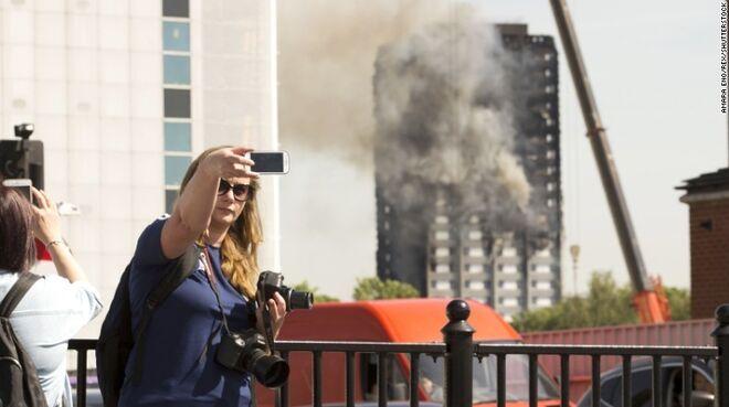 Turista se hace un selfie con la Grenfell Tower de Londres aún ardiendo.