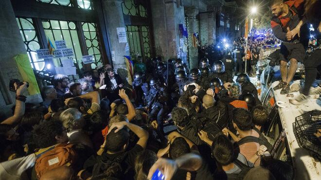 Agentes de los Mossos d'Esquadra custodian las puertas de la sede de la consellería de Economía de la Generalitat en cuyo interior se encontraba un grupo de agentes de la Guardia Civil.