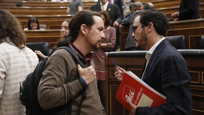 El secretario general de Podemos, Pablo Iglesias, conversa con el líder de IU, Alberto Garzón.