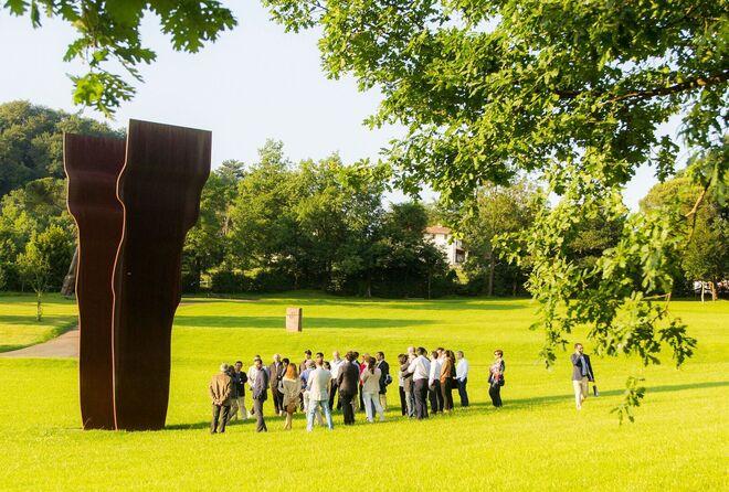 Un grupo visita Chillida Leku bajo la sombra de la obra  Buscando la luz I (acero corten, 1997).