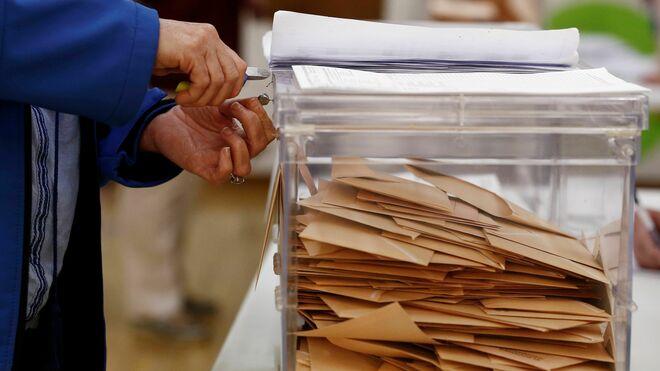 Una persona se dispone a quitar el precinto de una urna con las papeletas al Senado para proceder a su recuento en un colegio de la capital navarra