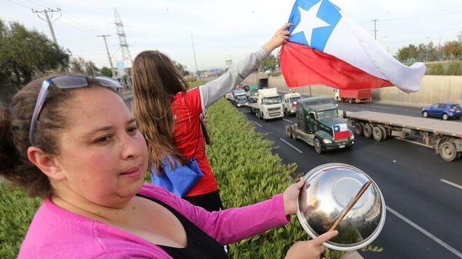 Ciudadanos muestran su apoyo a una manifestación de camiones y vehículos este viernes.