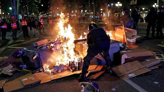 Los Mossos tratan de controlar una barricada de fuego durante los incidentes de Barcelona.