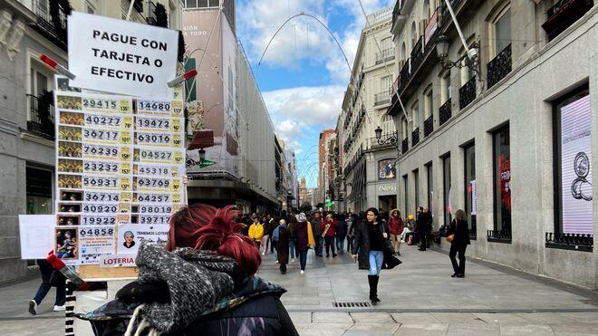 Una persona vende décimos de lotería en Madrid