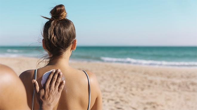 Mujer protegiendo su piel con crema solar