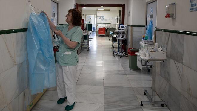 Una sanitaria coloca una bata en uno de los pasillos del Hospital Gregorio Marañón