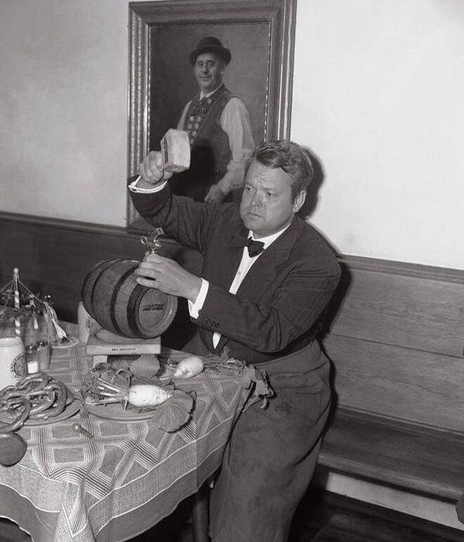 Orson Welles se prepara para abrir un barril de cerveza bávara con un martillo.