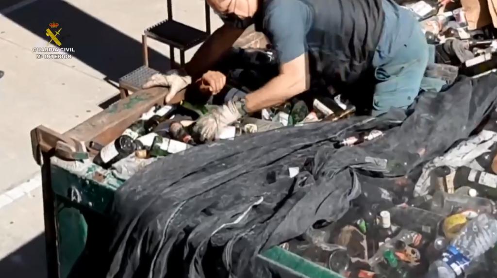 Imagen del guardia civil rescatando a un inmigrante de un camión lleno de cristales rotos.
