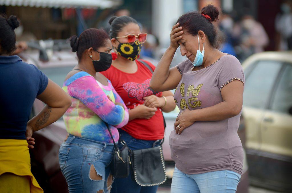 Una mujeres acuden a las cárceles de Ecuador tras los enfrentamientos.