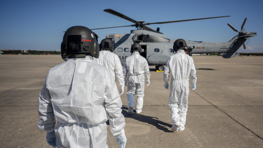 Varios militares totalmente protegidos se preparan para subir a un helicóptero.
