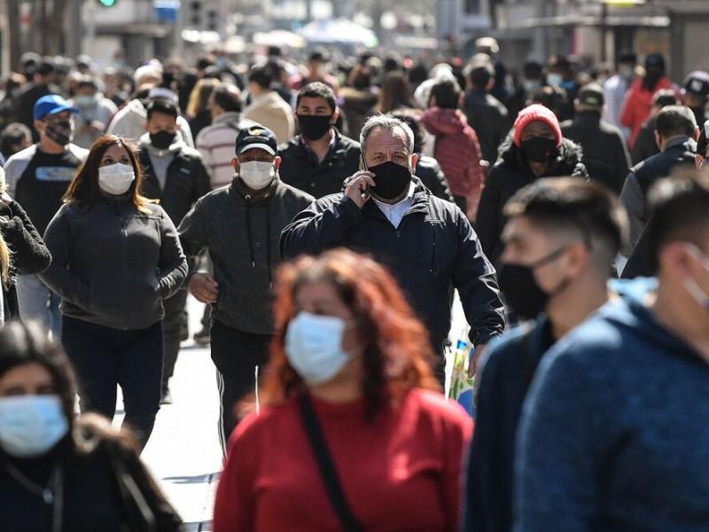 Gente pasea por la calle con mascarilla