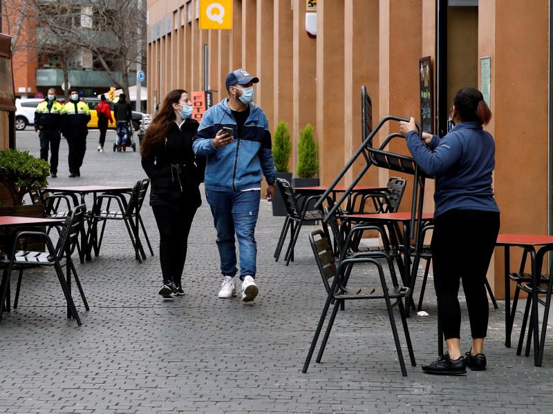 Una camarera prepara la terraza de un restaurante en Cataluña.
