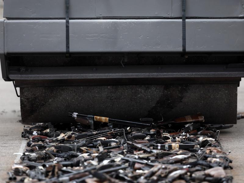 Una apisonadora pasa por encima de varias armas durante un acto de destrucción simbólica de casi 1.400 armas.