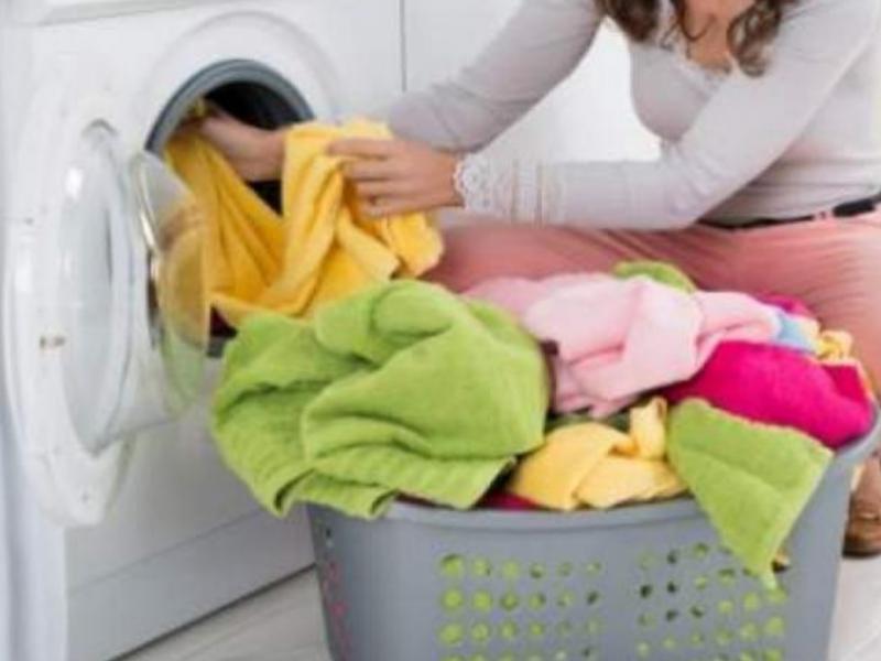 Una mujer saca la ropa de la lavadora
