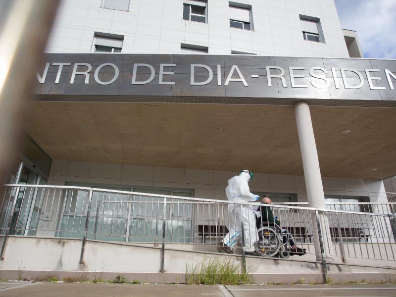 Un trabajador sanitario totalmente protegido acuden a buscar a un anciano de la residencia de ancianos de San Cibrao.