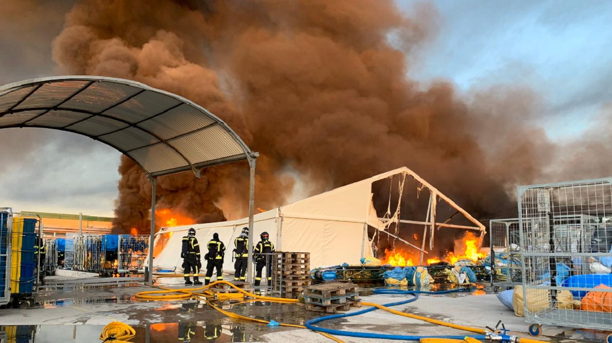 Los bomberos tratan de extinguir un aparatoso incendio en una nave industrial de Fuencarral (Madrid)