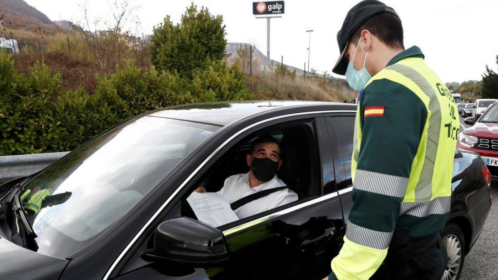 Un hombre muestra el justificante de movilidad a la policía