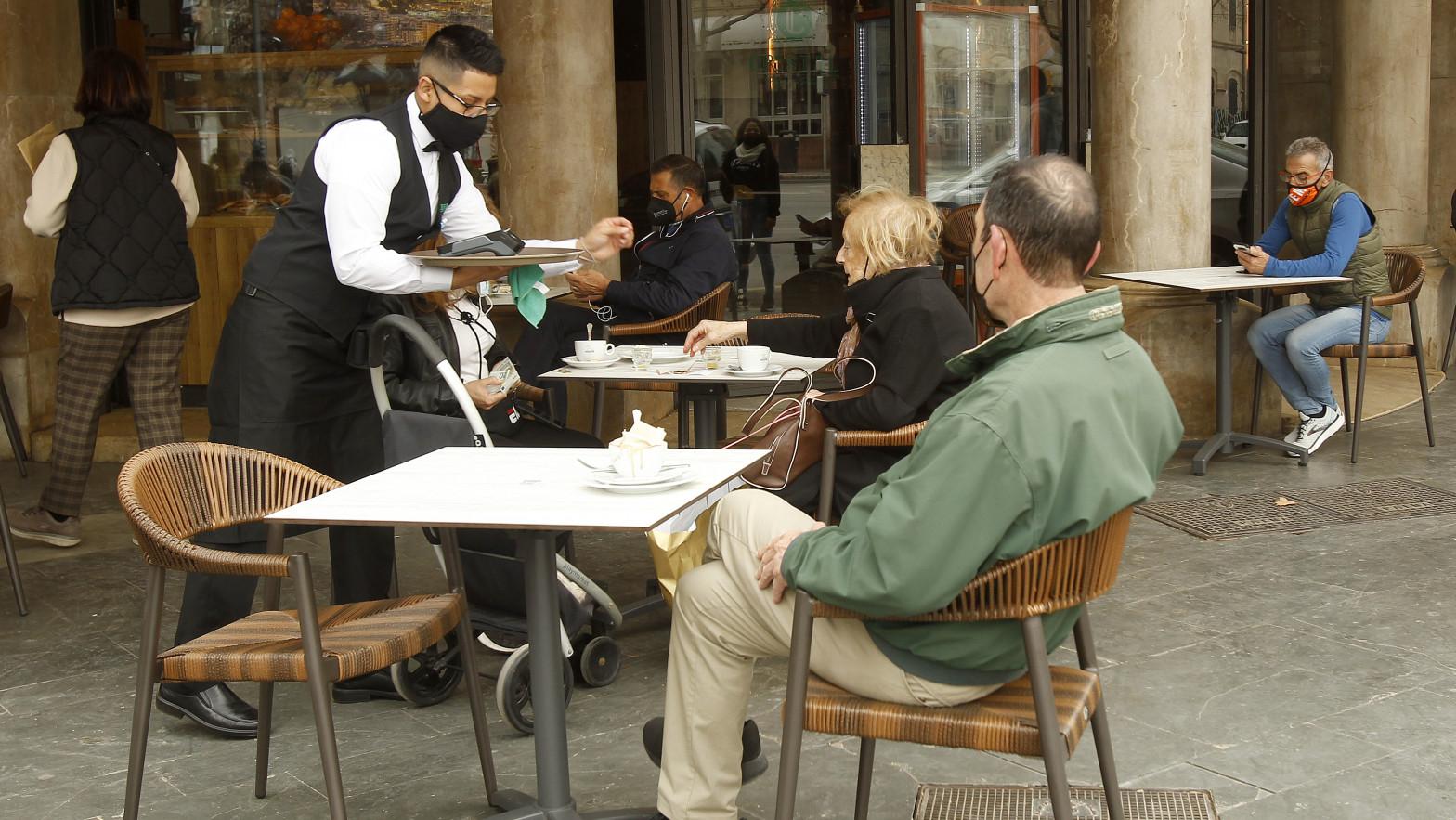 Camarero atiende en la terraza de un bar
