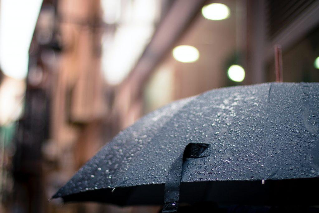 Un ciudadano caminando con un paraguas por el tiempo de lluvia.