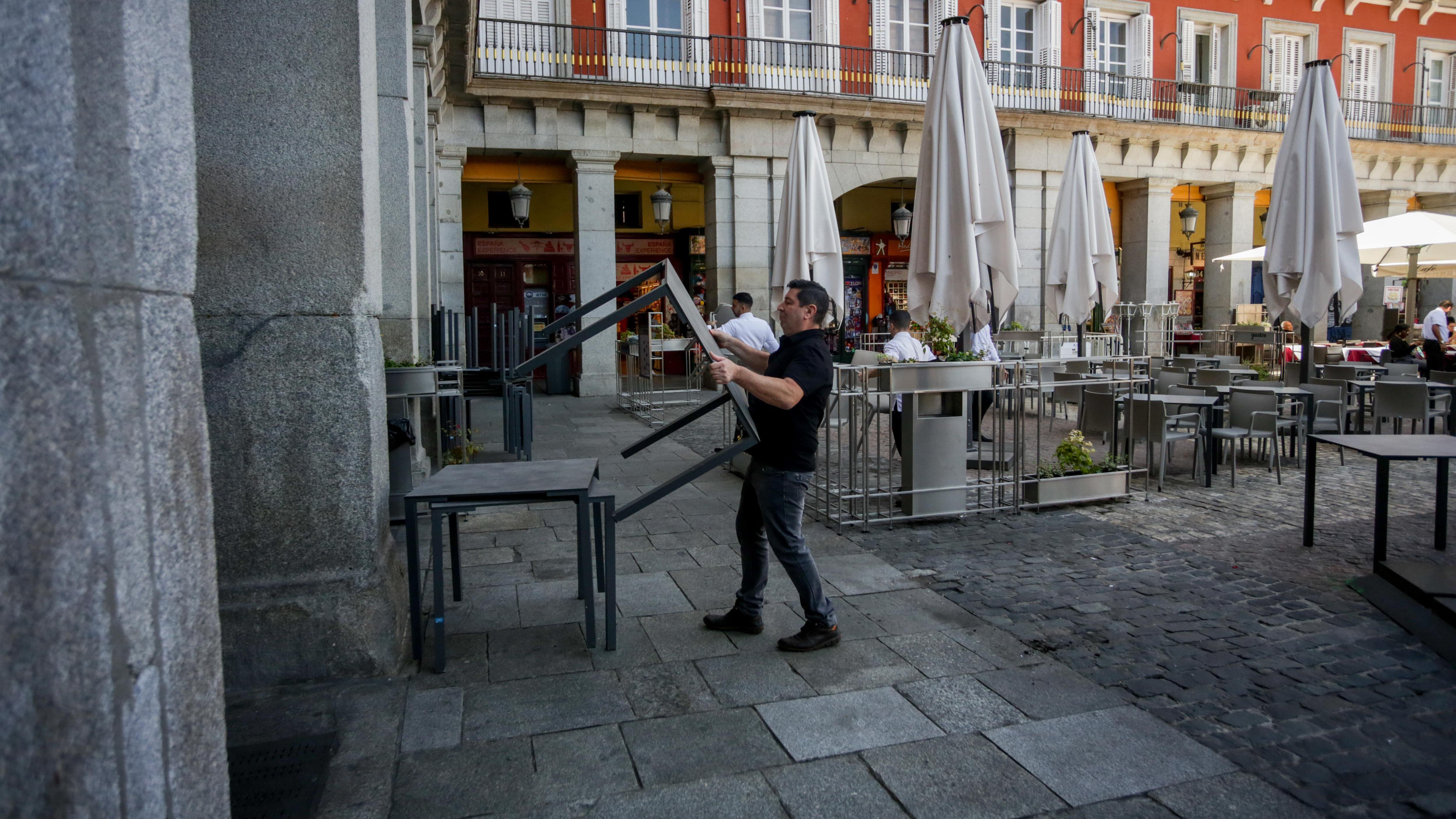 Un camarero coge mesas para la terraza del bar, en Madrid.