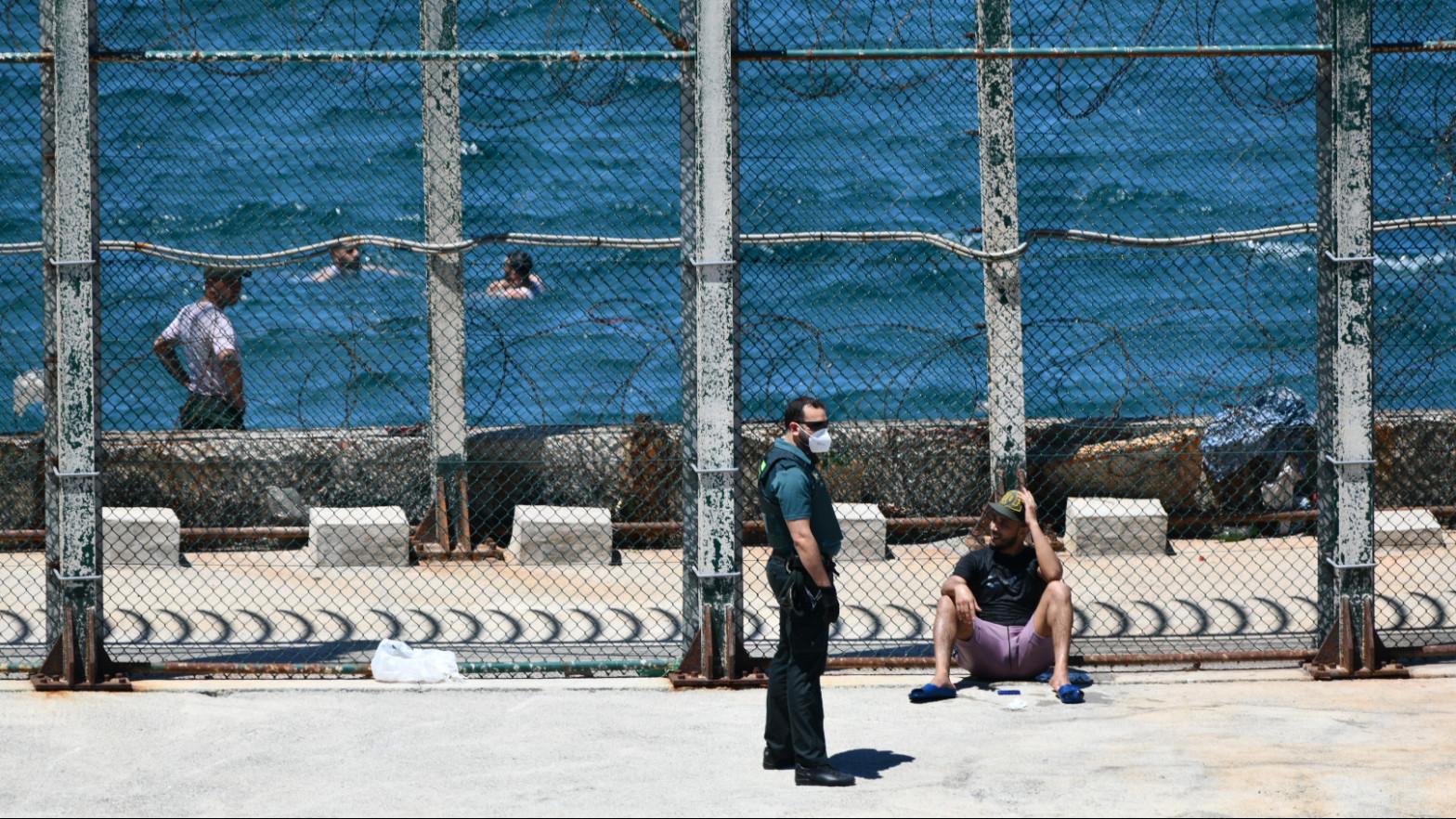 Un agente de Guardia Civil con un joven migrante marroquí en las inmediaciones de la valla de Ceuta, en la playa del Benzú