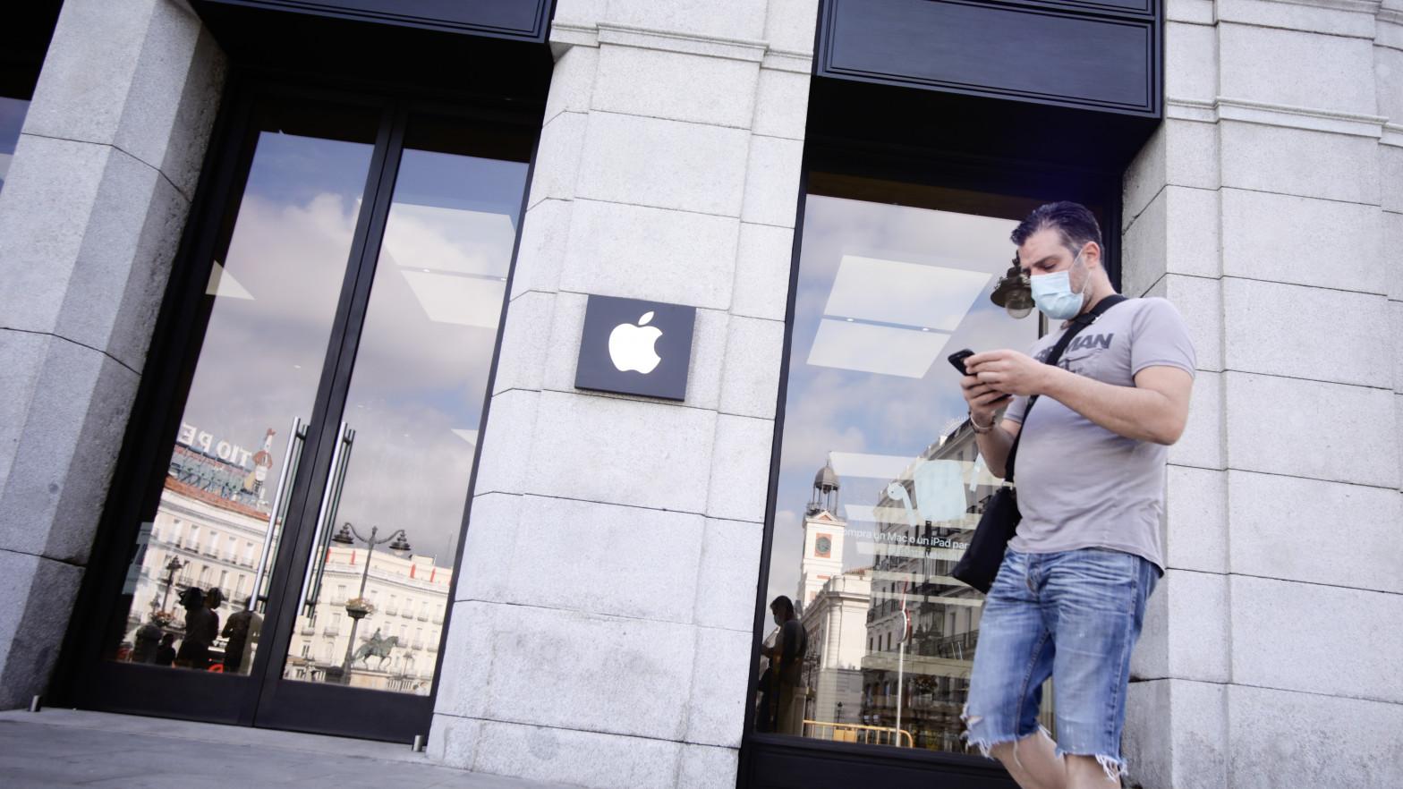 Una persona protegida con mascarilla pasa junto a la tienda Apple en la Puerta del Sol.