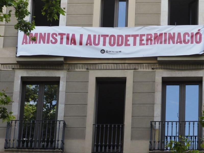 Òmnium despliega una pancarta ante el Liceo para reclamar a Pedro Sánchez amnistía y autodeterminación