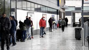 Decenas de personas protegidas hacen cola para poder entrar en un supermercado Lidl.